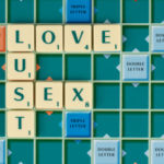 Scrabble tiles on a game board spelling the words Love, Lust and Sex