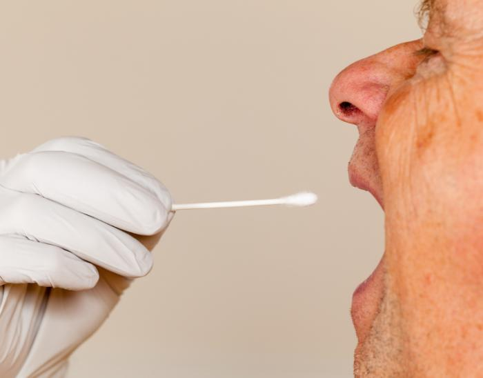 saliva swab being taken from man