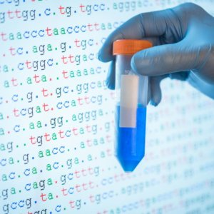 genetic testing shown by dna sample in front of screen showing code sequence