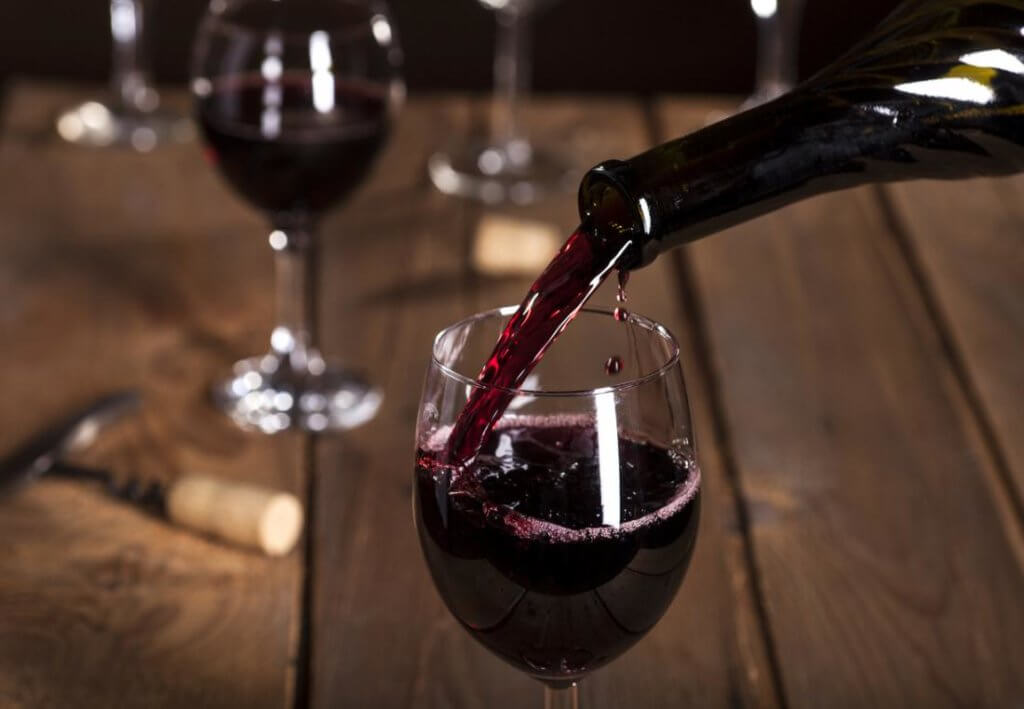 bottle pouring glass of red wine