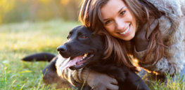 woman with dog black labrador smiling grass sunshine