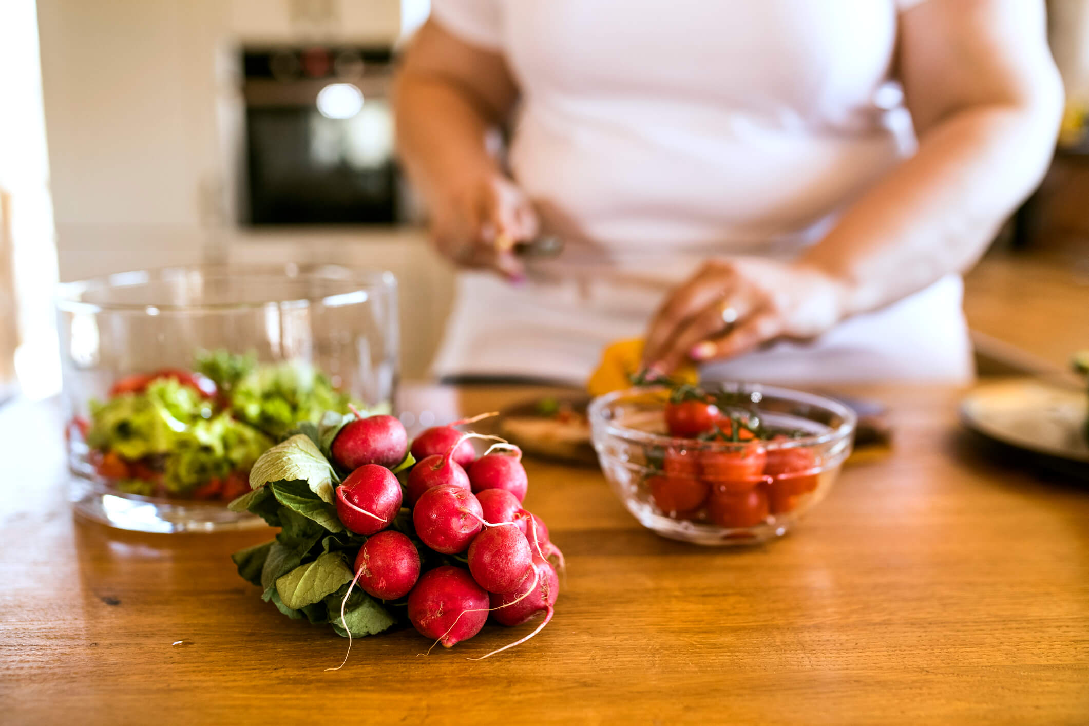 8-6-2018 Unrecognizable overweight woman at home preparing a delicious healthy vegetable salad in her kitchen.