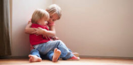 Unhappy Children Sitting On Floor In Corner At Home