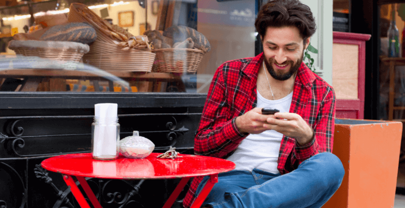 man looking at mobile phone in café e