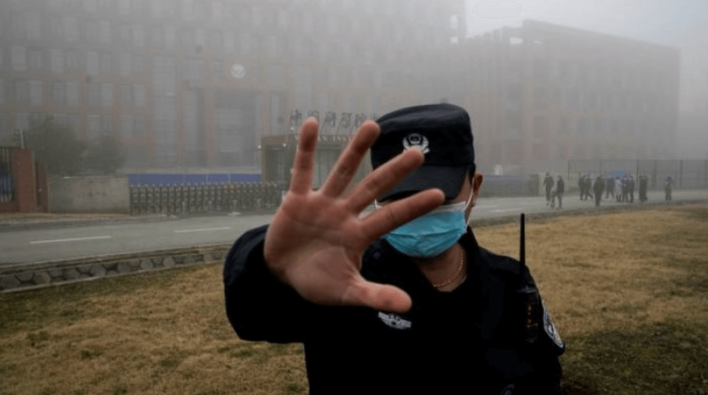 A security guard blocks journalists from the Wuhan Institute of Virology during a visit by World Health Organization investigators. Credit: AP