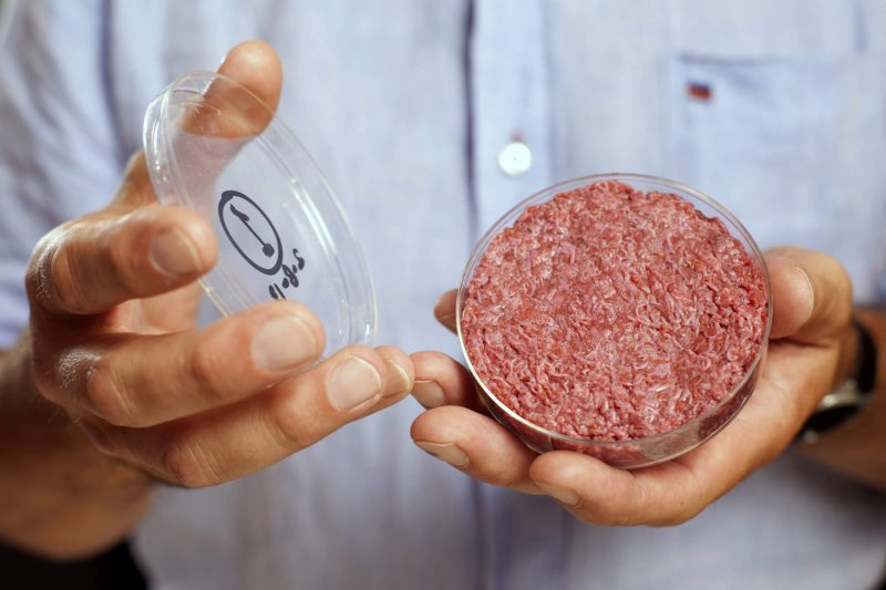 Professor Mark Post holds the world's first lab-grown beef burger. Credit: David Parry/Reuters