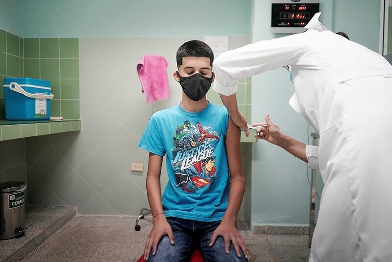 A healthcare worker at a hospital in Havana, Cuba, administers a dose of vaccine to a 14-year-old boy. Credit: Alexandre Meneghini/Reuters