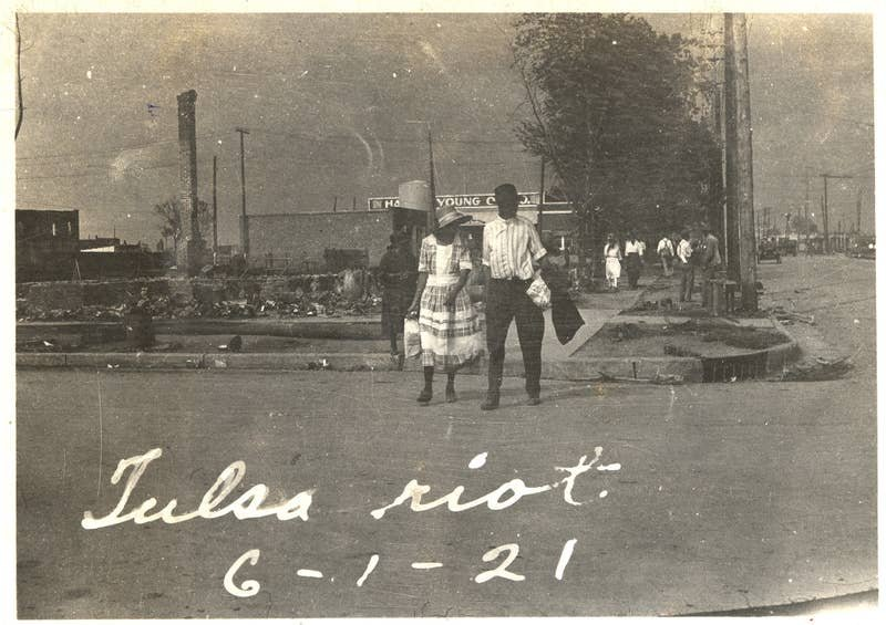 A couple walks across the street with smoke rising in the distance after the Tulsa massacre in June 1921. Credit: Oklahoma Historical Society/Getty Images