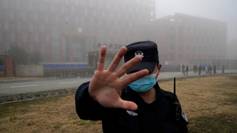 Security moves journalists away from the Wuhan Institute of Virology. Credit: Ng Han Guan/AP